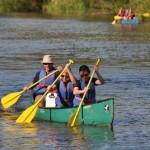 Team in einem Boot beim Paddeln. Dahinter Boot mit weiterem Team